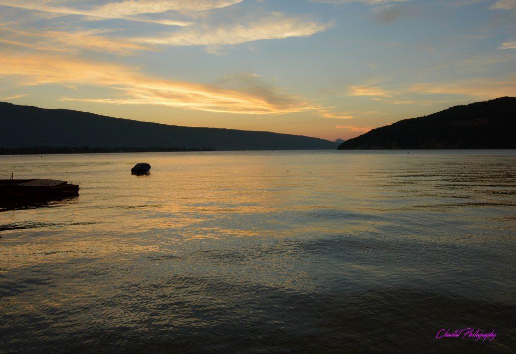 soleil couchant sur un lac entouré de collines