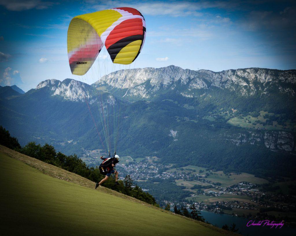 une personne saute en parapente devant un paysage de vallée surplombée de montagnes